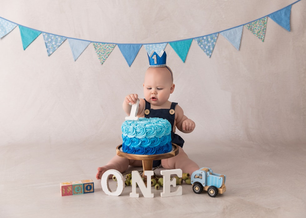 Baby playing with a wooden numeral at a cake smah photography session