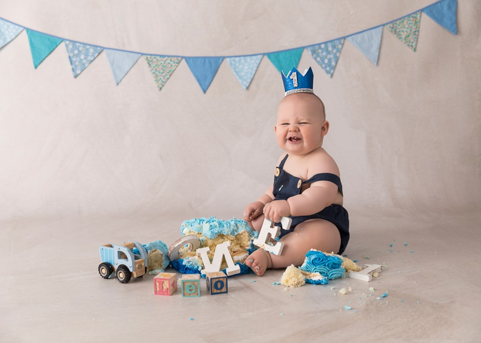 Grinning baby playing with wooden letters at a cake smah photography session