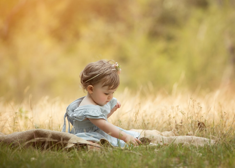A baby girl poses in a grass field for a kids photgraphy session by Howe Studios, Sydney