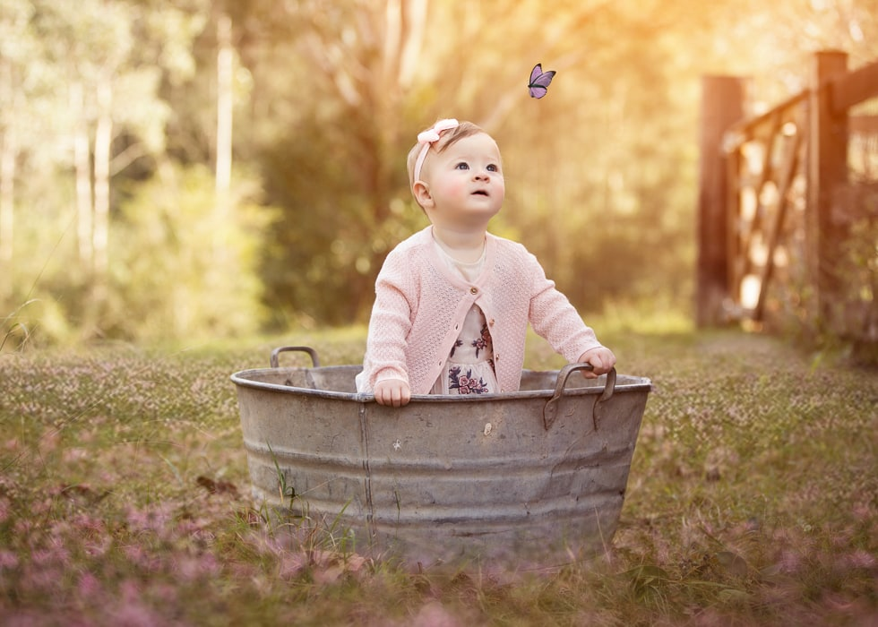 A baby girl stands in a steel bucket watching a purple butterfly during a kids photography session