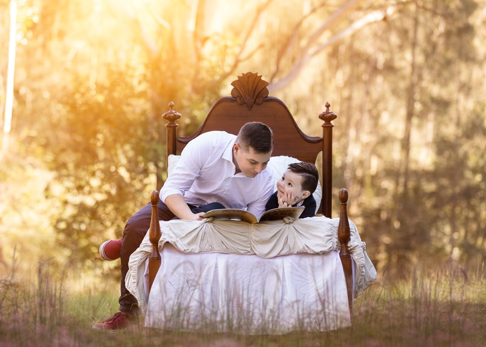 A father and son sitting on a wooden bed reading a book during a kids photography session