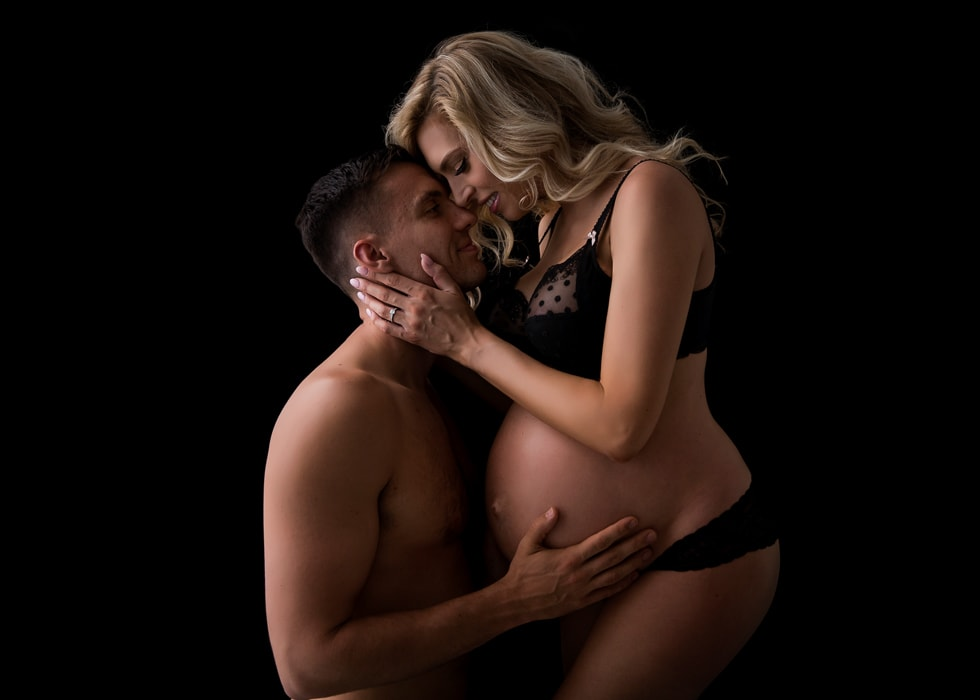 A young couple pose for a meternity photography shoot at Howe Studios, Sydney